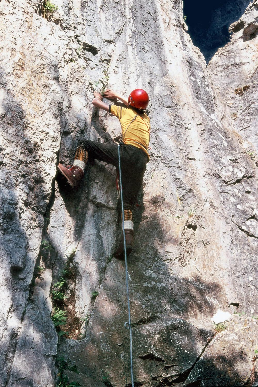 Iztok Tomazin na vstopu v smer Ta težka v Dovžanovi soteski leta 1975. Plezali so večinoma v gojzarjih, brez plezalnih pasov, vendar običajno s čeladami. Arhiv Iztoka Tomazina